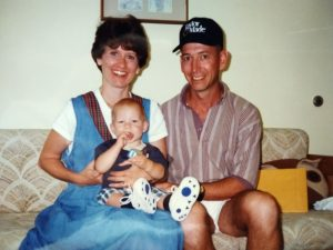adoption in the 1990s | mom and dad holding baby smiling on couch