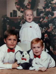 adoption in the 1990s | three siblings in front of a Christmas tree smiling