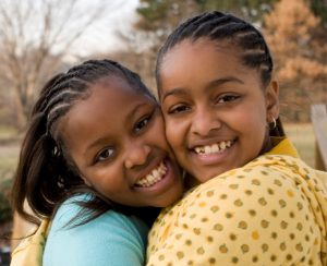 post adoption services | two young African American girls hugging and smiling