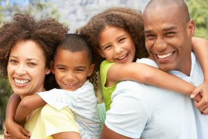 post adoption services | African American parents giving their children piggy-back rides smiling