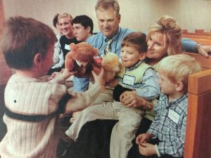 Open Adoptions | family of five sitting in a pew smiling, playing with teddy bears